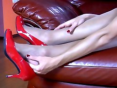 Long-legged lady in red pumps massages and sucks her tasty nylon clad feet