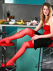 Bold chick wearing raunchy red stockings makes pussy spreads in the kitchen