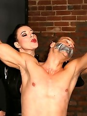 Spectacular domme Anastasia Pierce restrains her male submissive colleague with chains and duct gauze