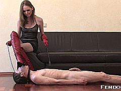 The glossy red boot that Mistress Angela has wedged into her boy toy's face
