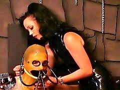 Mistress in latex dress roping a slave girl in bondage preparing her for training