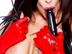 masked dominatrix in black and red latex with whip