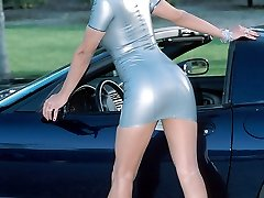 busty babe on Corvette in latex screw me dress