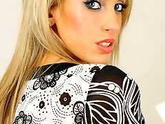 Blonde Ellie wearing a minidress with ebony stockings and suspenders
