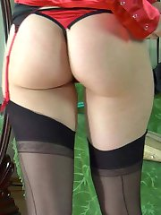 Blondie enjoys her reflection in the mirror wearing her back seam stockings