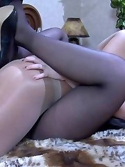 Passionate lesbian lovers launch into pantyhose slit licking on the sofa