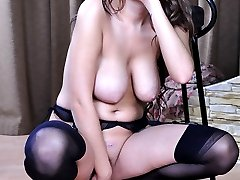 Busty babe in black seamed stockings and raunchy spike heels fucks her ass