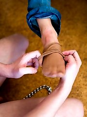Young slave learns to please his mistress by licking her little delicious toes through stockings.