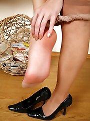 Leggy brunette hikes up her skirt examining sheer hose before changing them