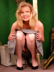 Blonde military girl in grey colored stockings and lengthy dress