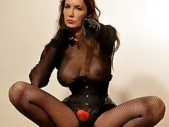 Gorgeous Femdom Strapon Jane is posing in fishnets with her favourite big red strapon cock