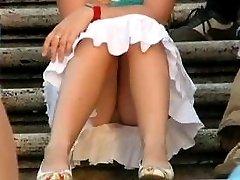 Russian girls flashtheir upskirt gems outdoors sitting in a sun-soaked park