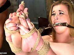 She is hot for the bondage and pussy play but she is super sensitive! So naturally the first thing to be done is to tie a vibrator on high, tight against her throbbing and swollen clit. She is tied up so tight that she can't possibly get away from it no matter how much she squirms and squeals.I decide to get her tight little cunt up front and center with her knees tied around her ears. The tiny clit vibe and giant dick on a stick ravage her super sensitive cunt till she is squirting uncontrollably and begging for mercy.She likes it doggie style. So I give it to her. She is tied like a little puppy girl, her back made to arch by tight ropes that push her now swollen and tender cunt into the air for us to fuck with a hard rubber dick till she gushes her squirt all over the floor.