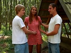 In the middle of the woods, this cute teen turns into a sloppy chick. She practically orders these 2 guys to tied her arms to the tree and use her in every way possible.