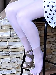 Adorable girl boasting her feet in white pantyhose after a heated shoe play