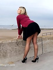 Gorgeous leggy blonde Naomi teases outdoors in a cute black summer dress, sexy nylon stockings...