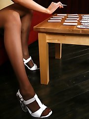 Vivacious chick scattering cards with her feet in toe reinforced pantyhose