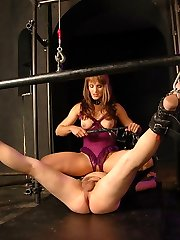 Mistress in purple fetish lingerie sits on slaves face and fucks him with a strapon cock