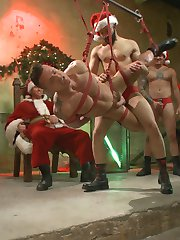 Santa's hosting a big party, and he's invited everyone to help him judge whether this whore called Rex Cameron has been naughty or nice. Bad Santa in a black robe rolls into the party and makes it clear that Rex has been nothing but dirty this year. Proving his point, Rex hungrily gags on Bad Santa's enormous dick. Made to wear a chastity cage, Rex gets passed around the crowd until Santa's little helpers show up and stuff two cocks into his mouth. Rex gets on his knees and rims more of Santa's boys to the party's roaring delight until Bad Santa gets up to fuck his naughty hole. As he takes Bad Santa's dick, Sebastian fits Rex's mouth with a dildo gag and rides the slut's face. Bad Santa trades out with one of his dudes as another covers Rex's face in cum. The crowd decorates his body in clothespins and ornaments with zip lines attached. As Rex submits to his treatment, the crowd tears them away. Santa's helpers drag Rex back to Santa's throne and swing him from dick to dick in a sideways suspension over the party. Mr. Claus jerks his hard cock, presiding over Bad Santa and crew taking turns fucking the trapped whore and glazing his face in holiday cum.