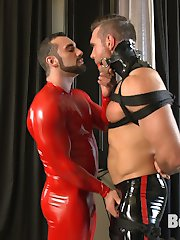 A bronzed, muscular slave stands clad in latex and bound in rope, awaiting the ministrations of his master. First, his large cock is unzipped from his tight rubber shorts and his chest, cock and balls are cropped mercilessly before his well-hung master decides it is time to fuck his sub's face with his hefty dick. Next our hot latex slave is suspended and subjected to intense ball stretching and flogging, his screams echoing as he struggles helplessly at the mercy of his master. A harsh metal electrostim butt plug is inserted in the slave's hungry asshole and his hard cock bounces as his prostate is shocked again and again, though nothing could prepare his hole for the hard, fast fucking he receives from his master's huge cock - while being shocked and fucked the slave can't contain himself any longer and blows a huge load all over himself, only to get even messier with his master's thick hot cum.