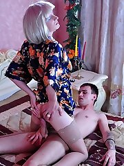 Crossdressed platinum blonde in a flowery robe and red thong in queer twosome