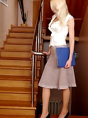 Dazzling blonde hikes up her skirt changing into brown hose on the stairs