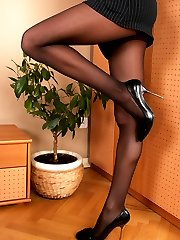 Lovely chick playfully raising her feet clad in reinforced toe pantyhose