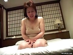 Asian granny inserts a sex tool in her pussy