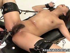 Fastened Oriental handles sex machines like a trooper