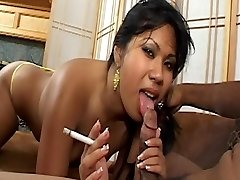 Asian babe with cute tits smokes cigarette and gets jizm facial on couch