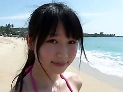 Slim Japanese girl Tsukasa Arai walks on a sandy beach under the sun