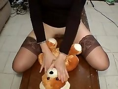 Gorgeous gal in stockings rides a bear bear on a table