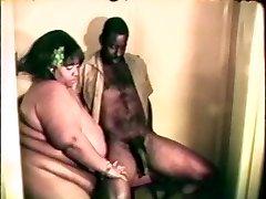 Big fat hefty black whore enjoys a hard black cock between her lips and legs