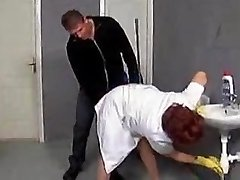 Mature cleaner enticed on the toilet floor