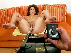 Fat cougar lady is testing a new sex machine with her legs spread wide open