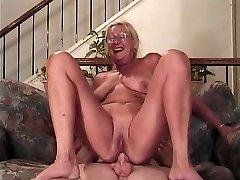 Reife Blondine mit Brille lutscht einen Schwanz