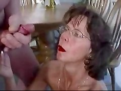 Mature dark-haired in glasses fosters huge facial cumshot.