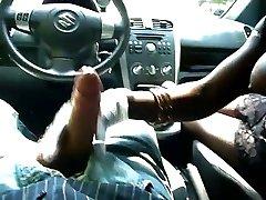 Zwarte meid met grote tieten geeft handjob in de auto