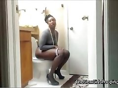 Ebony  girl crapping on the toilet