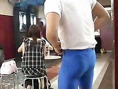 Muscular guy flashes very cute busty Japanese chick in a bar