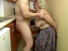 Insatiable, blonde granny is toying with her tits and her lovers cock, in the kitchen