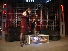 Two mistresses predominate their caged slave girl