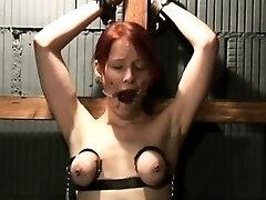 Pretty redhead masochist stands brutal breast torment