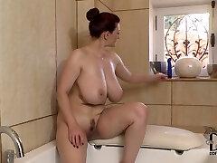 Well stacked brunette milf faux-cock fucks her bosom in the bath room