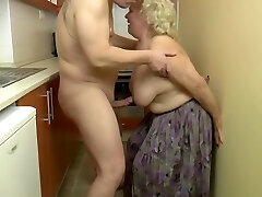 Insatiable, towheaded granny is playing with her titties and her lovers dick, in the kitchen