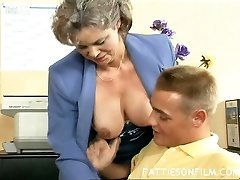 Volutuous grey haired grannie Kelly fucks her young boy in the office