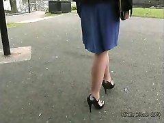Hete blonde heeft mooie benen en een sexy paar hoge hak schoenen op