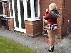 Brandus kaimynas vaikšto su trumpais sijonas ir plikas asilas lauke