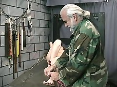 Cute young brunette with tattoo is restrained by Master Len in dungeon