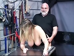 Rondborstige slaaf zuigt haar master's pik in de folterkamer